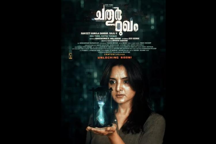 Manju Warrier holds an hour glass in her hand against a dark background and film title and crew details are written on top