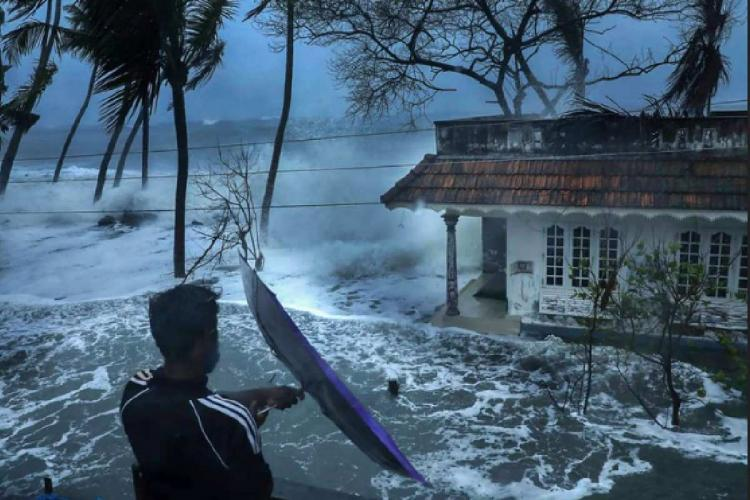 Man standing in front of a house hit by coastal erosion