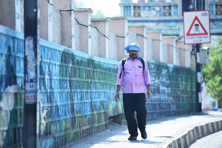 Man walks in the heat with a handkerchief on head