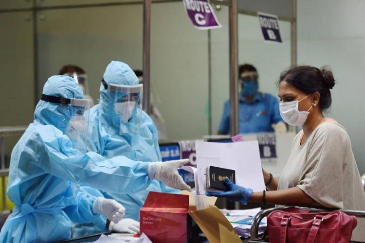 A woman passenger at the airport extending passport and other documents in her left hand to two airport officials in PPE suits