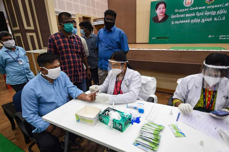 Two doctors wearing face shields sit in a fever camp in Chennai as one man gets checked for symptoms of COVID-19