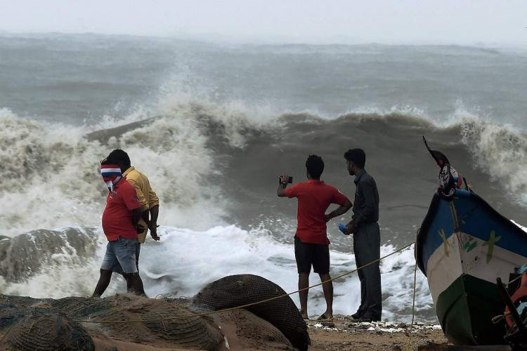 People at Chennais Marina beach as strong waves hit the coast triggered by Cyclone Vardah which made landfall on the coast of the Bay of Bengal in Chennai