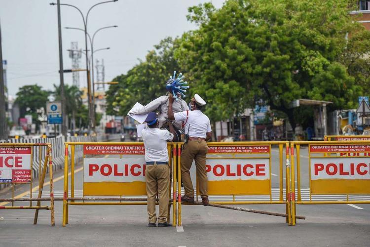 Two police men holding up a coronavirus effigy near a barricade in Chennai