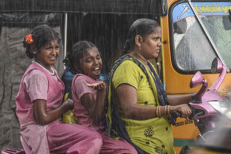 Commuters ride on a two-wheeler during an unseasonal rainfall in Chennai