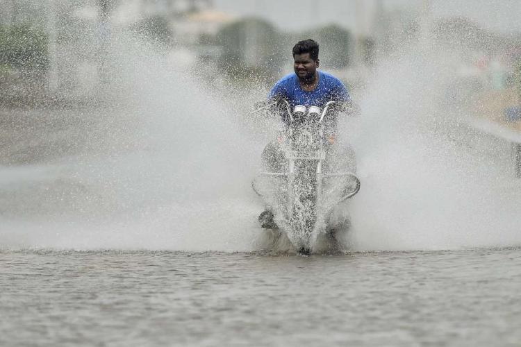 A motorist rides through a waterlogged road after heavy rain in Chennai Thursday Oct 29 2020