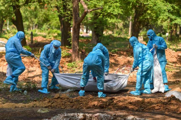 A group of people wearing blue PPE kits is carrying the body of a COVID-19 victim in a white sheet at a crematorium