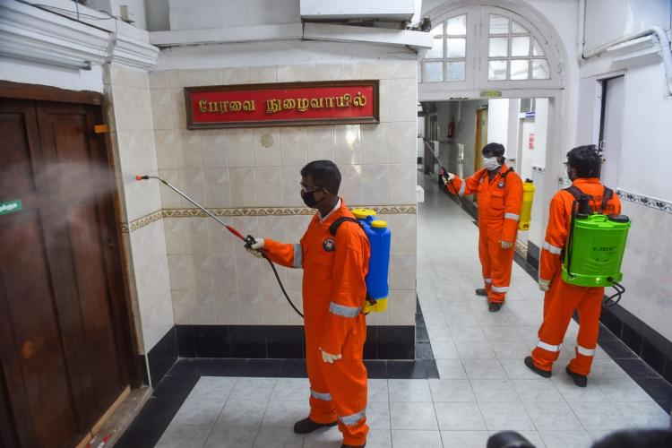 Workers in orange hazmat suit sanitising the Tamil Nadu Assembly building in Fort St George Chennai which was closed after a few tested positive Workers are spraying disinfectants on the doors and floors of the building