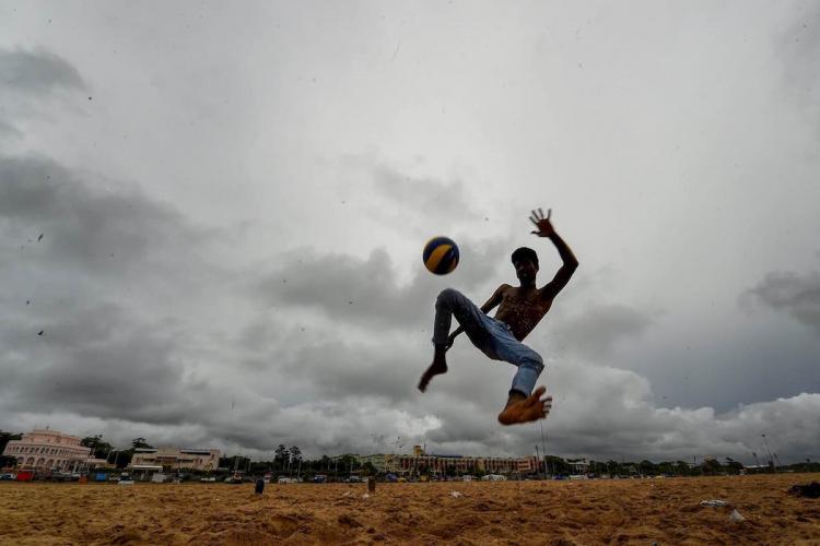 A boy kicks a football mid-air on a cloudy day at Marina beach in Chennai