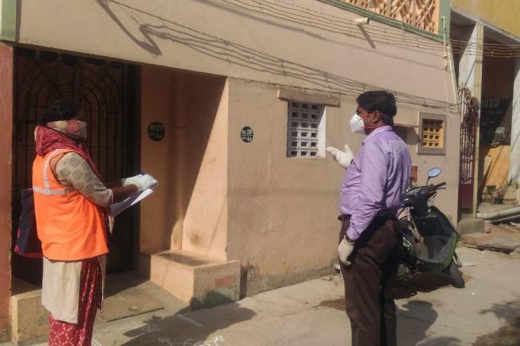 Surveyors wearing face masks outside a house in Chennai