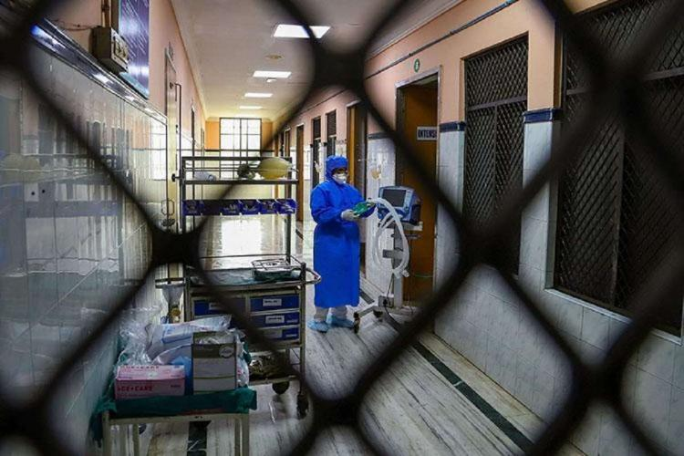 health worker through wire mesh at a hospital