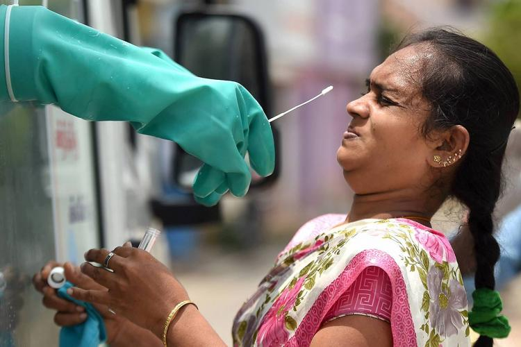 Woman recoils from a gloved hand trying to take a swab sample for covid testing in Chennai