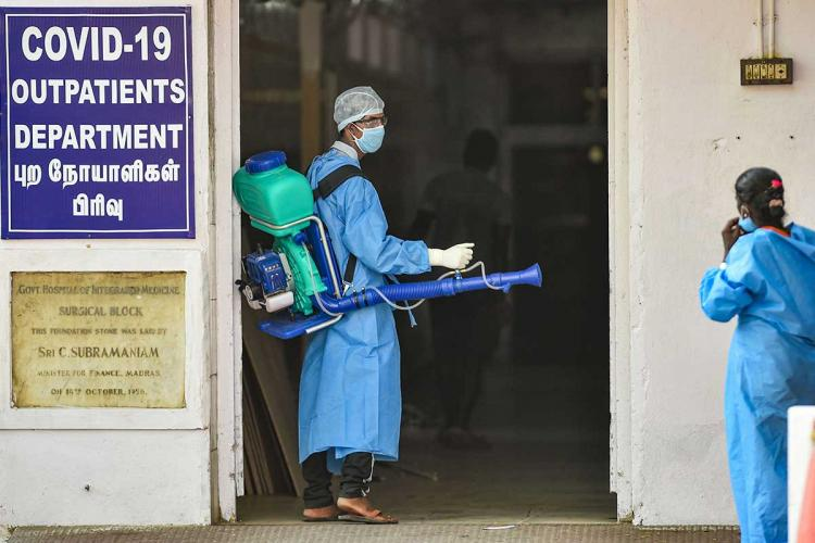 A staff at a hospital in Chennai is disinfecting the premises He is geared up in the PPE kit He is seen speaking to a woman who is also in a PPE kit