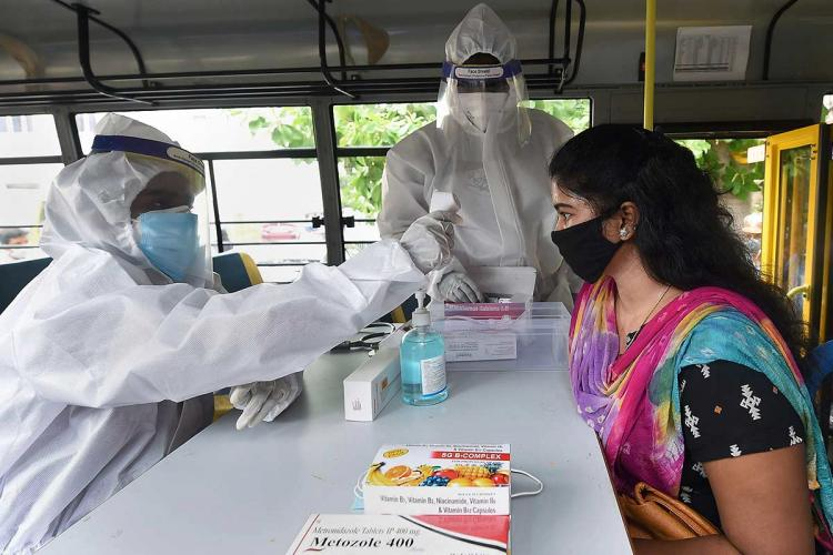 A woman in a salwar kameez wearing a mask sitting at a table with some drugs on it having her temperature screened by a health worker in a PPE suit while another health workers stand by