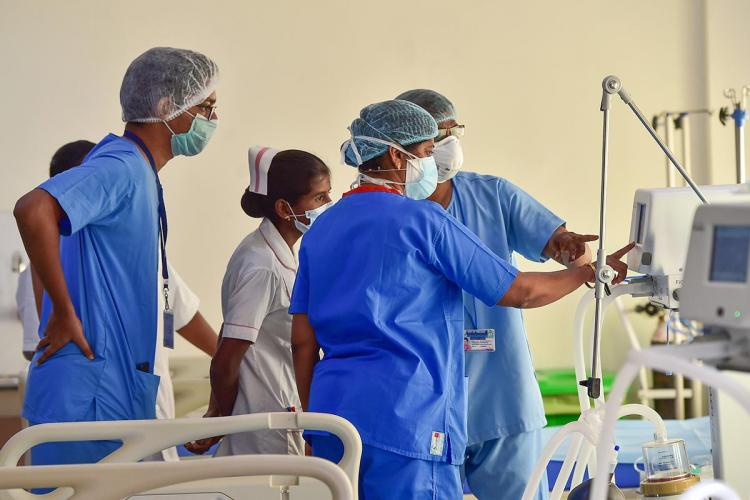 healthcare workers look at a monitor in a chennai hospital