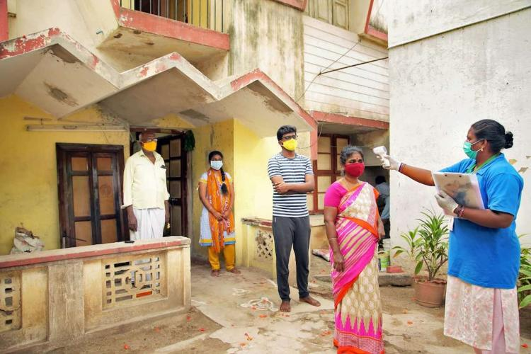 Health worker checks temperature for a family in chennai as father son daughter and mother stand outside their house