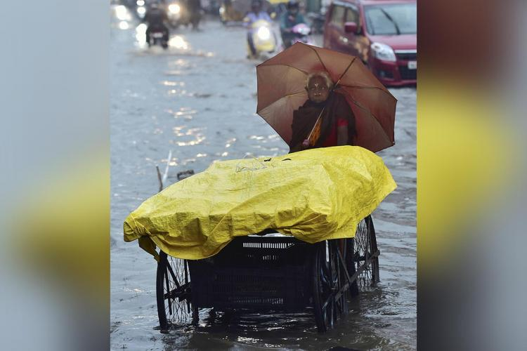 An old woman pushes a pushcart as she holds an umbrella and wades through waters in Chennai