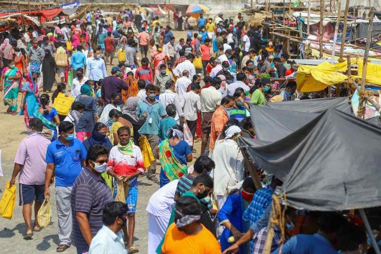 People crowding in a market in Chennai in the early days of lockdown due to COVID-19 Residents are wearing masks sporadically and shopping for vegetables and other essentials