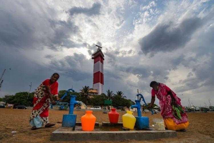 A group of women pumping water in the pump before the light house as the clouds are getting darker