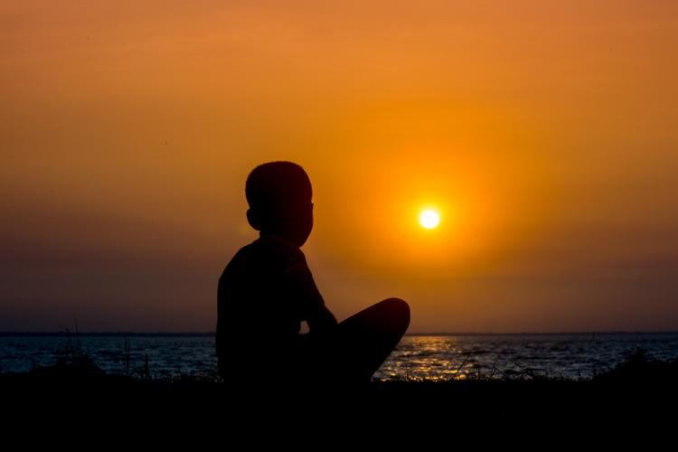 Silhouette of a boy against the sunset at a sea shore in India
