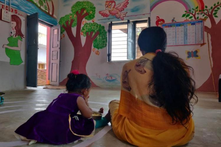 A mother and child at a child care Anganwadi centre run by women and child welfare department