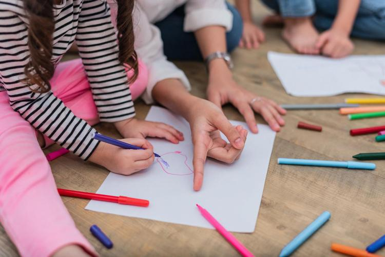 A child and mother painting and drawing on a white sheet of paper with crayons and sketchpens around
