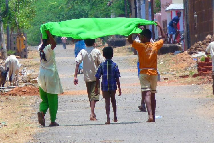 A group of children hold up a piece of cloth to shield themselves from the sun
