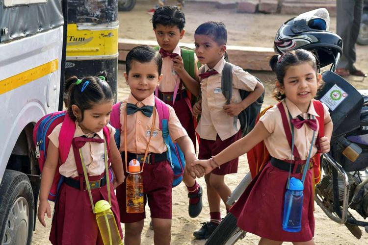 Five primary school children in their uniform on their way to school some have water bottles