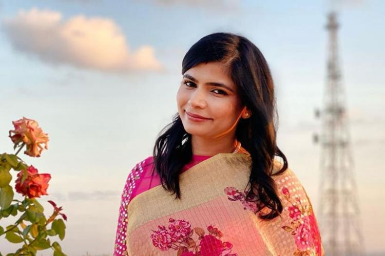 Chinmayi wearing a floral saree Flowers in the foreground and a cell phone tower seen in the background