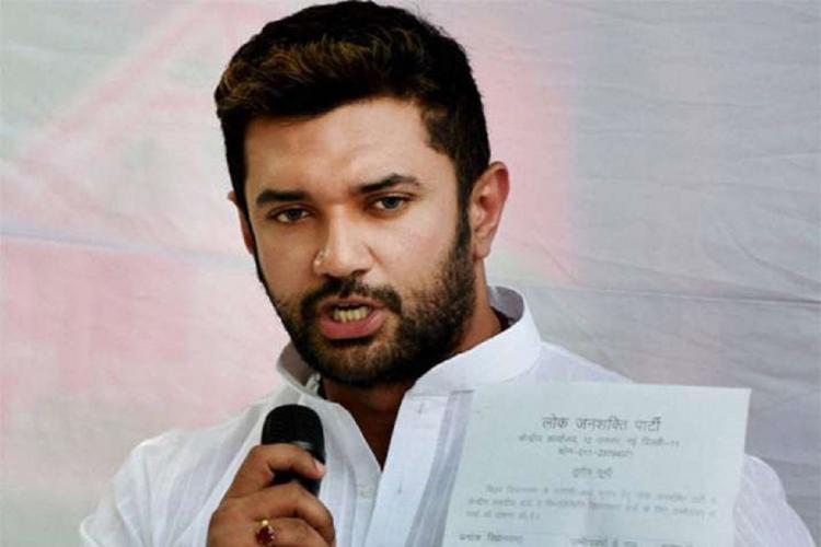 Chirag Paswan wearing a white kurta and white shawl He is holding a mic while speaking and a paper in his left hand