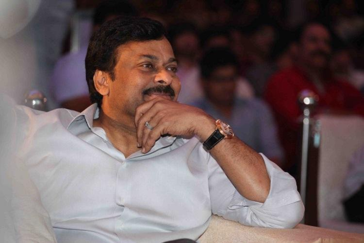 Chiranjeevi wearing a white shirt has a hand on his chin and looks away