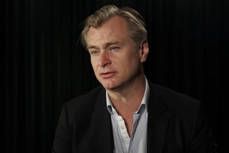 Hollywood filmmaker Christopher Nolan wears a dark jacket and light shirt while posing for a photo