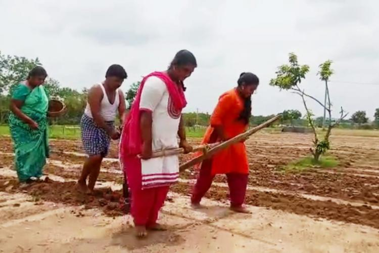 A farmer and his wife ploughing their field while their daughters pull the yoke in front of them