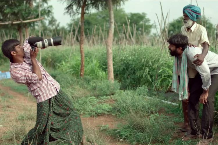 A screenshot from Cinema Bandi where a man is trying to take a photo of two other men in a field