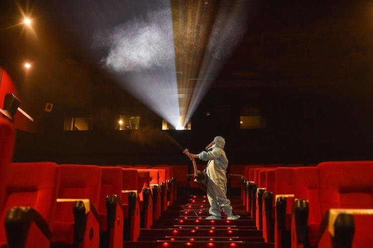Cinema theatre being sanitised by a worker in white hazmat suit