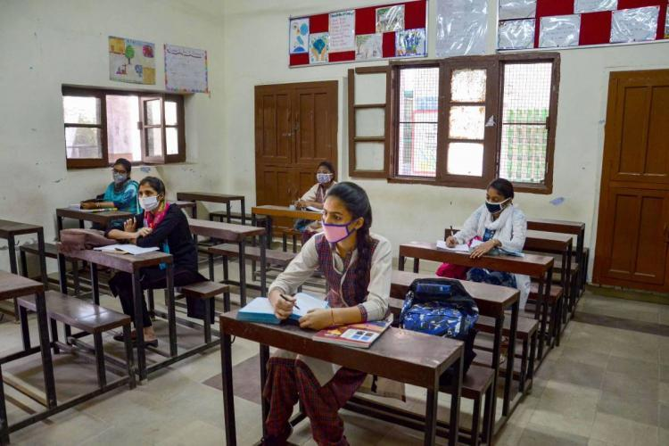 Students wearing masks seated in a classroom at desks maintaining distance