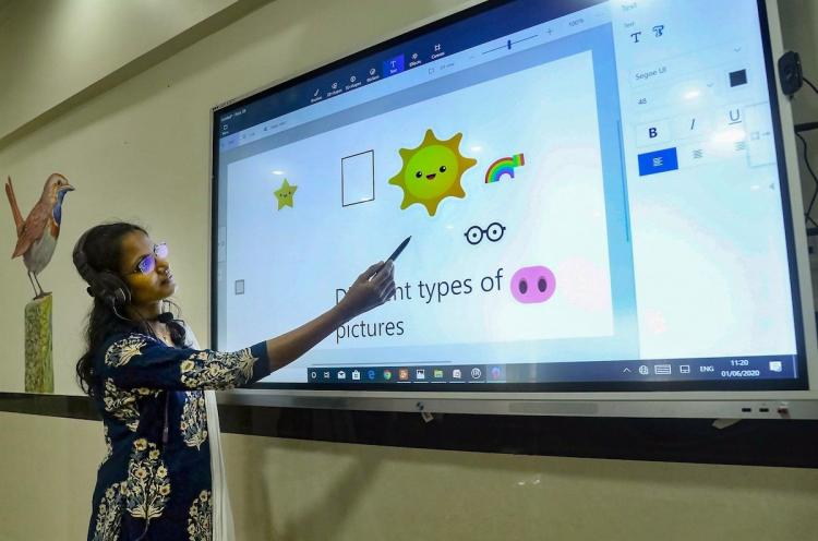 Teacher taking online class for students using smart board