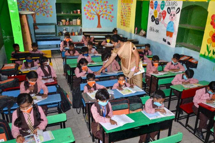 Students wearing masks attend a class after schools resumed for the students of classes 1st to 5th in Mirzapur