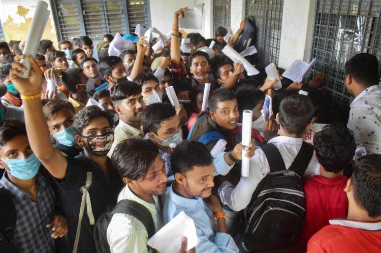 Students checking thier result in a college by wearing thier masks and college bags