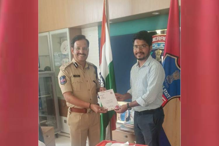 Plantable Wedding card is being presented to Commissioner in uniform by Shashikanth in formals