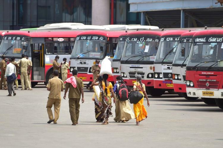 Women carrying luggage on their heads walk alongside bus conductors in the Bengaluru Bus Station in the background are several parked ksrtc buses
