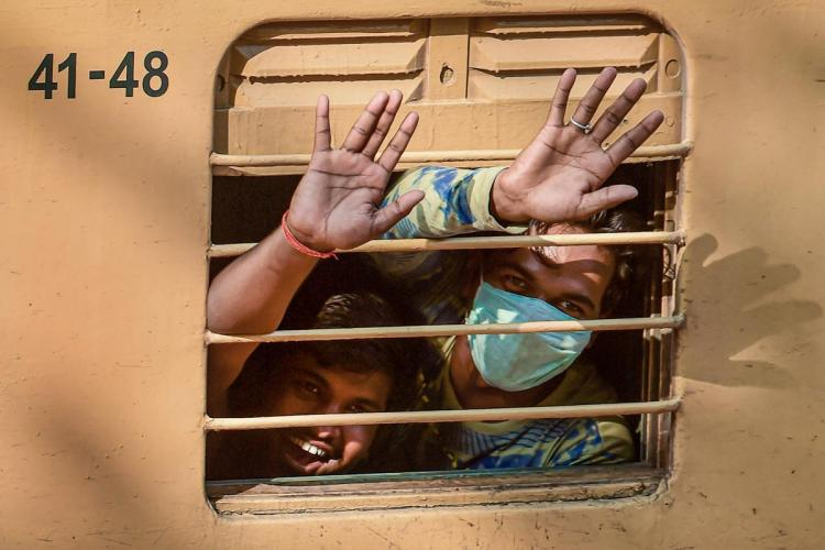 Two migrant workers waving from inside the train