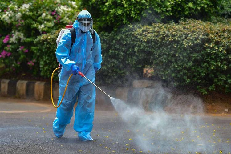 Sanitary worker in blue hazmat suit spraying sanitiser on road
