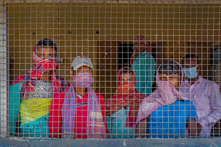 A group of migrant workers look out from inside a grilled corridor