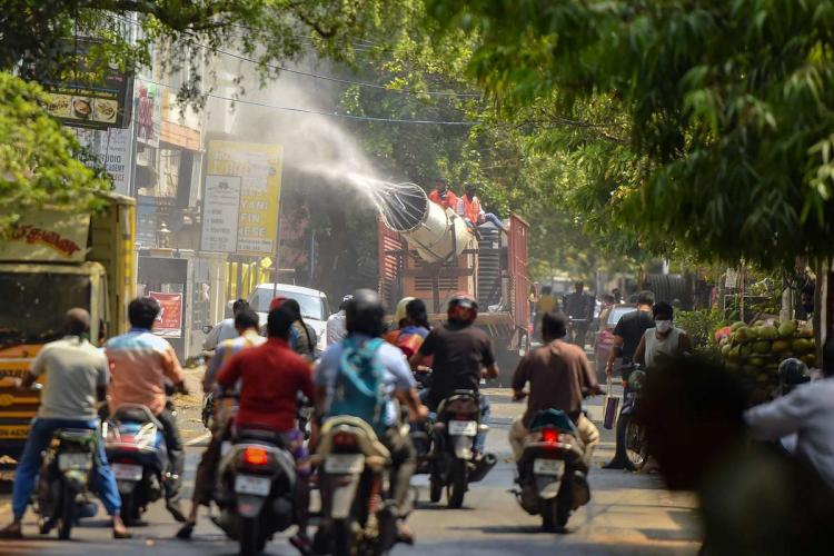 a truck sprays disinfectant on the road while scooters and motorcycles wait for the vehicle to pass