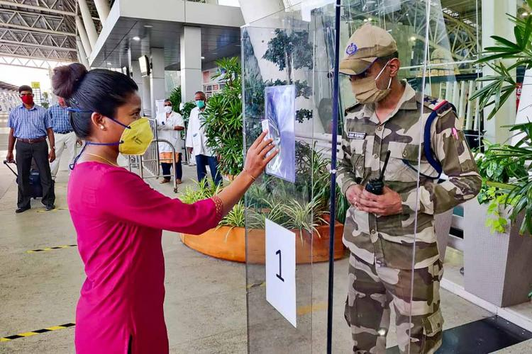 A passenger displaying her flight details to the security personnel at Chennai airport