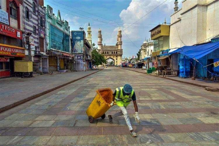 A disaster management personnel carrying out disinfection drive in the streets of Charminar area in Hyderabad