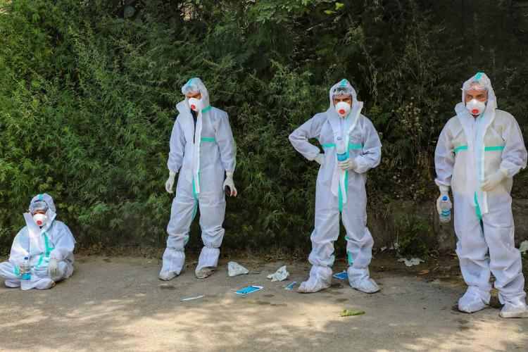 Four health workers seen wearing personal protective equipment and one of them sitting down while the other three stand