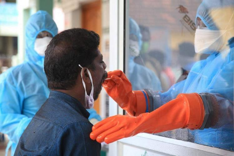 A health worker wearing mask and gloves collecting sample from a man for coronavirus test