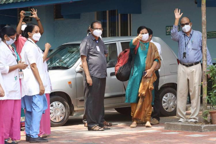 Recovered COVID-19 patients waving after being discharged from Kozhikode hospital