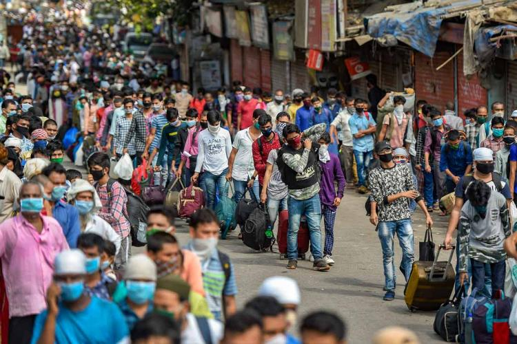 Migrant workers line up to leave with their luggage in Mumbai